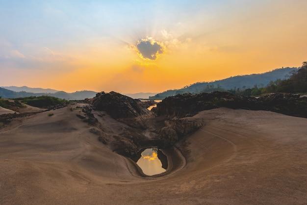 Paysage coucher de soleil sur la plage de sable fin avec rocher et ciel orange Photo Premium