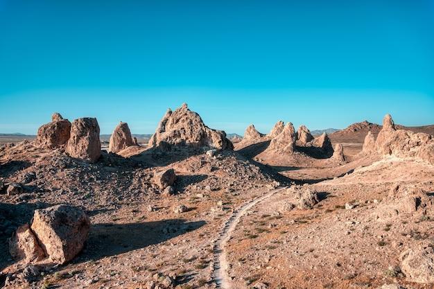 Paysage D'un Désert Avec Route Vide Et Falaises Sous Le Ciel Clair Photo gratuit