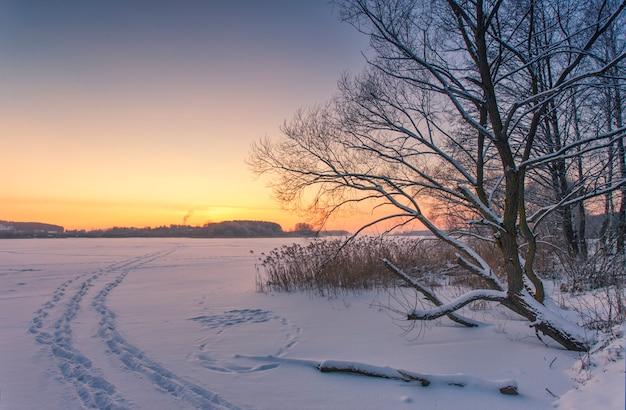 Paysage Du Lac Couvert De Glace En Hiver Avec Les Empreintes De Pas De Personnes Dans La Neige Au Coucher Du Soleil Photo Premium