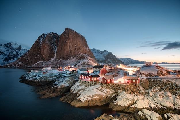 Paysage du village de pêcheurs de la maison rouge avec la montagne au lever du soleil Photo Premium