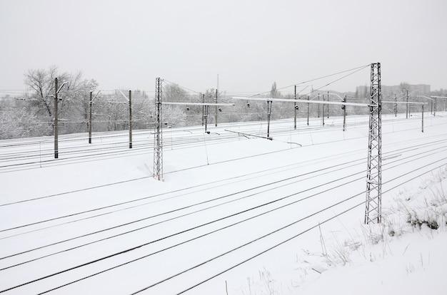 Paysage ferroviaire d'hiver, voies ferrées dans le pays industriel enneigé Photo Premium