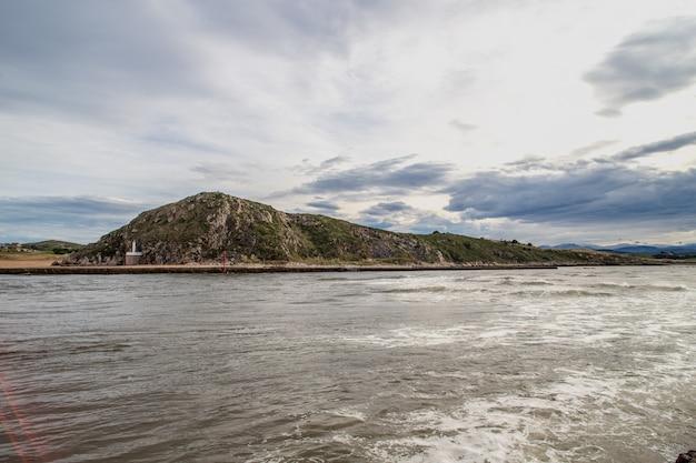 Paysage maritime avec des montagnes verdoyantes et un ciel nuageux Photo Premium