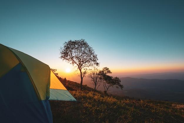 Paysage de montagne au coucher du soleil avec tente de camping. Photo Premium