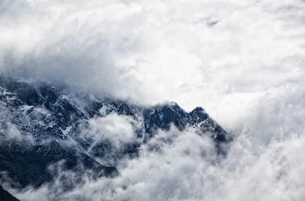 Paysage de montagne avec brouillard et ciel nuageux Photo gratuit