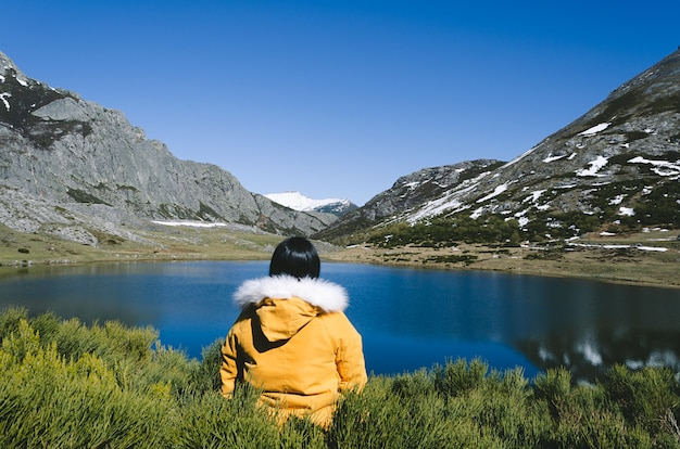 Paysage De Montagne Avec Montagnes Enneigées Et Lac. Femme Au Manteau Jaune Regardant Le Lac. Lac Isoba, Leon. Espagne. Photo Premium