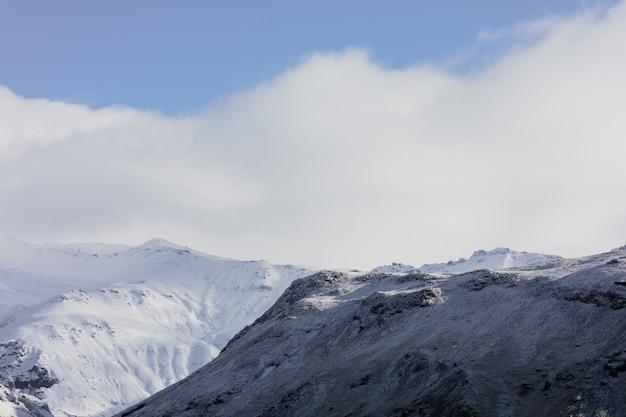 Paysage De Montagnes Couvertes De Neige Sous Un Ciel Bleu Nuageux En Islande Photo gratuit