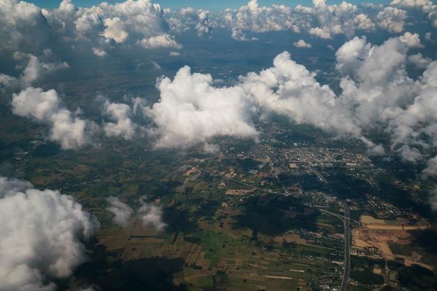 Paysage de la terre vu de l'avion. surface de la terre sous les nuages blancs de vue aérienne. Photo Premium