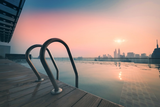 Paysage Urbain De La Ville De Kuala Lumpur Avec Piscine Sur Le Toit De L'hôtel Au Lever Du Soleil En Malaisie. Photo Premium
