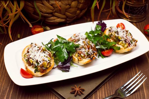 Peaux de pommes de terre remplies de champignons, d'oignons, d'herbes, de légumes et de fromage fondu Photo gratuit