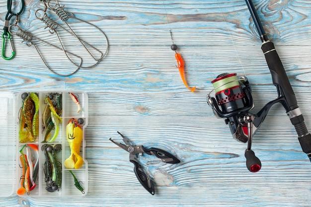 Pêche filature, hameçons et leurres sur fond bleu en bois. vue de dessus Photo Premium