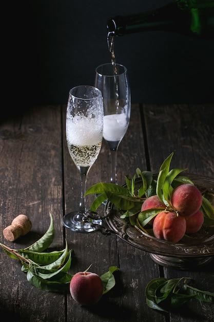 Pêches Sur Branche Avec Champagne Photo Premium