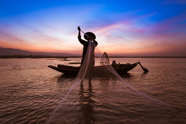 Pêcheur asiatique avec son bateau en bois dans la nature rivière tôt le matin avant le lever du soleil Photo Premium
