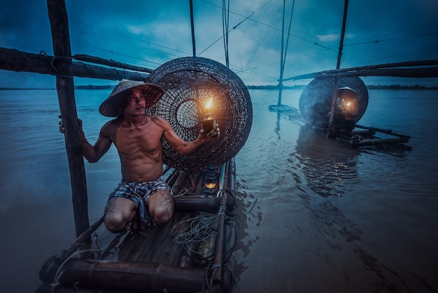 Pêcheur asiatique tenant une lanterne sur son bateau en attente de pêcher dans le mékong. au crépuscule Photo Premium