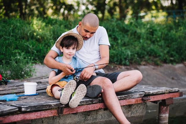 Pêcheur assis sur la jetée avec son fils pêchant sur le lac Photo gratuit