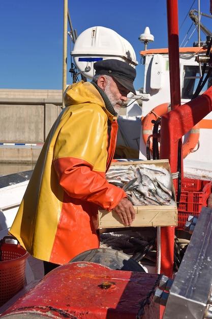 Pêcheur avec une boîte de poisson à l'intérieur d'un bateau de pêche Photo Premium