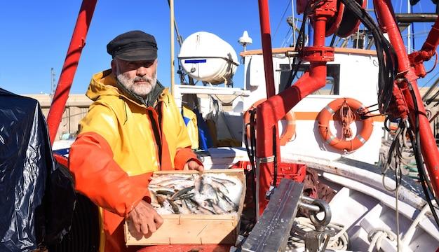 Pêcheur avec une boîte à poisson à l'intérieur d'un bateau de pêche Photo Premium