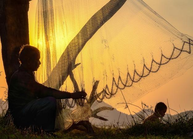 Pêcheur commercial réparant ses filets de pêche. Photo Premium