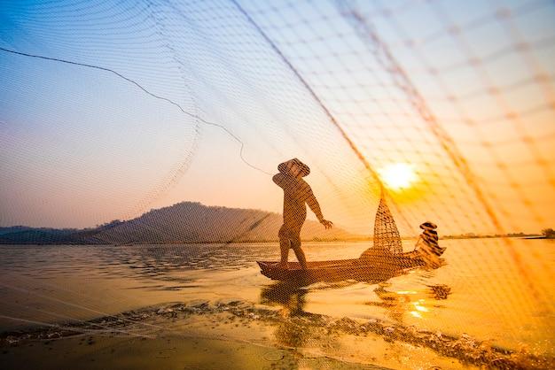 Pêcheur sur le coucher du soleil de la rivière de bateau Photo Premium