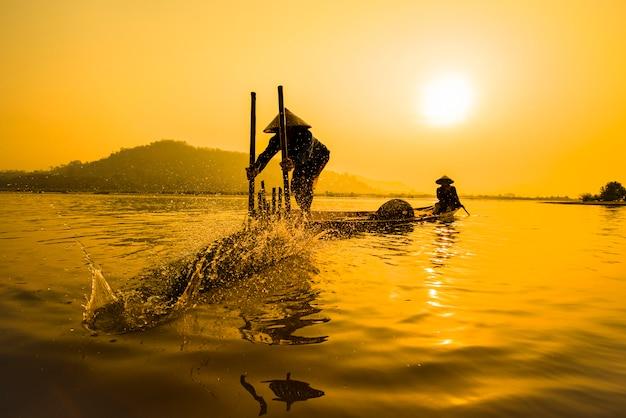 Pêcheur, sur, rivière, bateau, coucher soleil, asie, pêcheur, bambou, poisson, piège, sur, bateau, coucher soleil Photo Premium