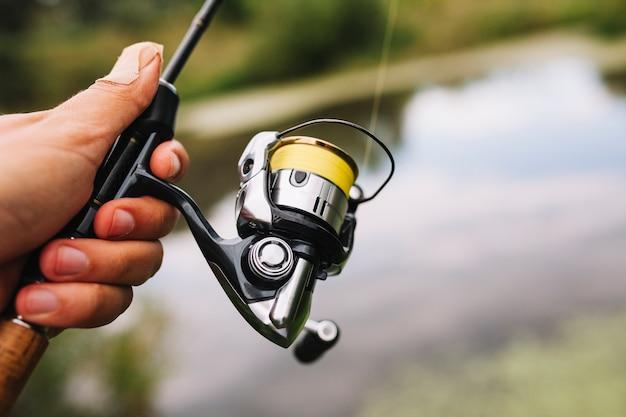 Pêcheur, tenue, canne à pêche, sur, arrière-plan flou Photo gratuit