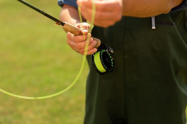 Pêcheur utilisant un moulinet à tambour avec une ligne jaune Photo Premium