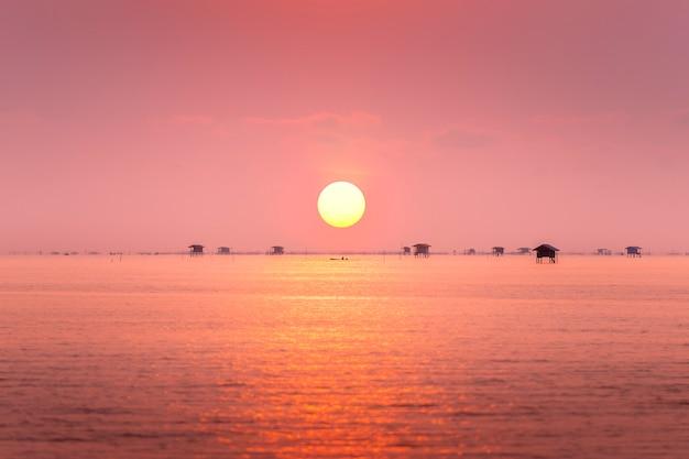 Pêcheur Et Village Flottant Dans L'océan Au Lever Du Soleil Photo Premium