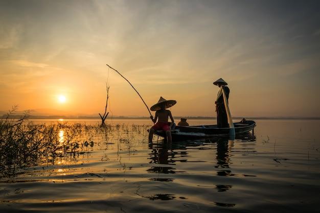Pêcheurs une canne à pêche avec un crochet vont pêcher tôt le matin avec un boa en bois Photo Premium