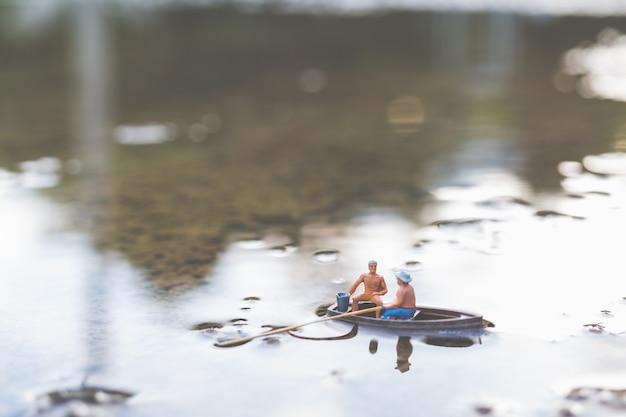 Les pêcheurs miniatures pêchent en bateau Photo Premium