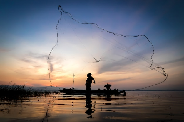 Les pêcheurs qui pêchent commencent à pêcher tôt le matin avec des bateaux en bois et une vieille lanterne Photo Premium
