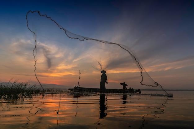 Les pêcheurs qui pêchent commencent à pêcher tôt le matin avec des bateaux en bois Photo Premium