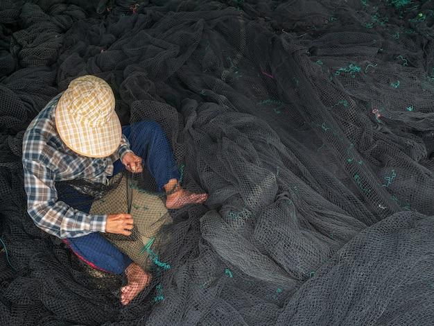 Des pêcheurs réparent des filets de pêche, un pêcheur du port en train de réparer des filets Photo Premium