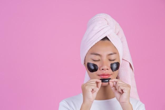 Peeling cosmétique beauté. jeune femme avec un masque pelable noir sur la peau, produit de peeling cosmétique pour le soin de la peau sur le visage, de couleur rose. Photo gratuit