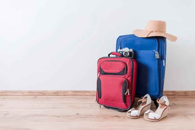 Peep-toe chaussures et chapeau près des valises et caméra Photo gratuit