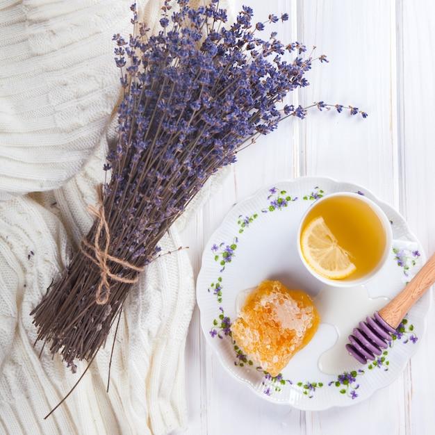 Peigne à miel sur une assiette avec les couleurs de la lavande et du thé au citron Photo Premium
