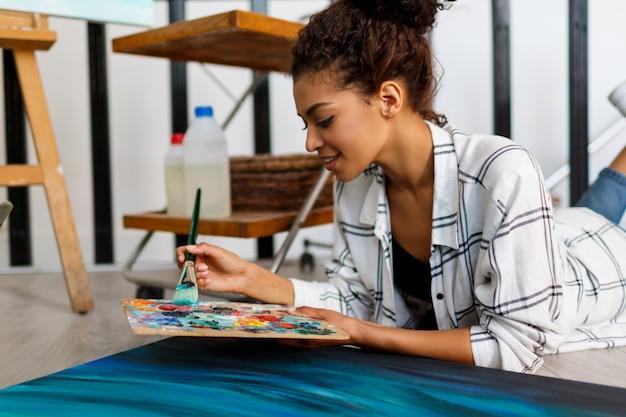 Peintre Femme Gisant Sur Le Sol Près De La Toile Et Du Dessin Intérieur Du Studio D'artiste. Fournitures De Dessin, Peintures à L'huile, Pinceaux D'artiste, Toile, Cadre. Concept Créatif. Photo gratuit