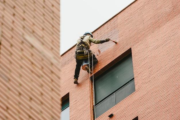 Peintre perché accroché aux murs d'un bâtiment avec des cordes. Photo Premium