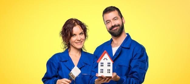 Peintres tenant une petite maison sur fond coloré Photo Premium