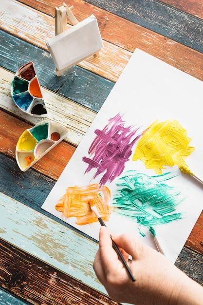 Peinture de la personne sur du papier blanc sur du bois texturé Photo gratuit