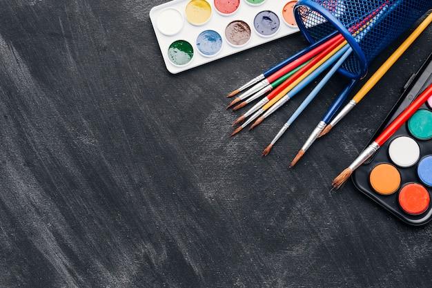 Peintures brillantes et pinceaux sur fond gris Photo gratuit