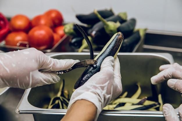 Peler La Peau Noire Des Aubergines Photo gratuit