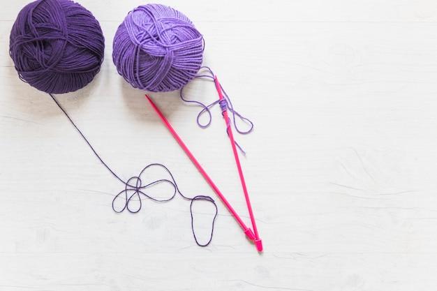 Pelote de laine avec une aiguille tricotée rose sur fond texturé blanc Photo gratuit