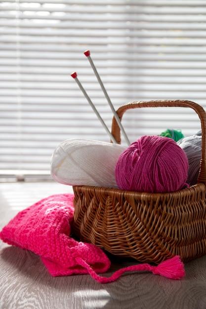 Pelote de laine et des aiguilles à tricoter dans le panier sur une table en bois grise avec la lumière de la fenêtre. fait main. Photo Premium