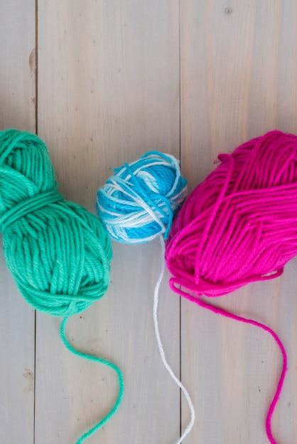 Pelote de laine colorée sur un bureau en bois Photo gratuit