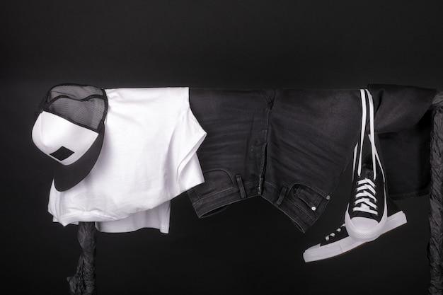 Pendre des vêtements. baskets noires et blanches, casquette et jeans sur étendoir sur fond noir. Photo Premium