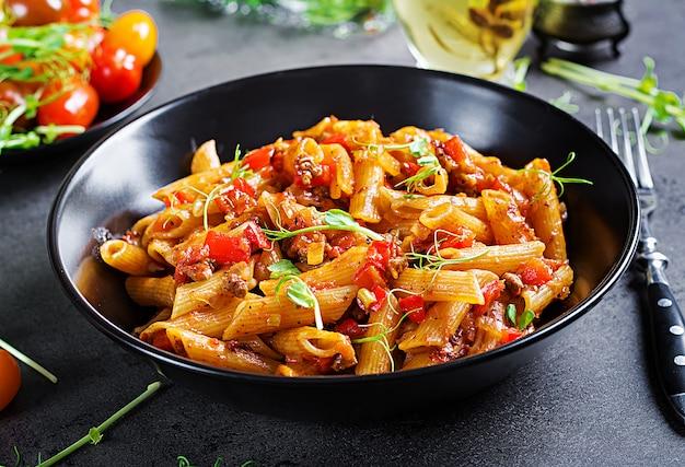 Penne à la sauce tomate avec de la viande, tomates décorées avec des germes de pois sur une table sombre Photo Premium