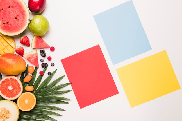 Pense-bête jaune-bleu rouge et différents fruits à la feuille de palmier Photo gratuit