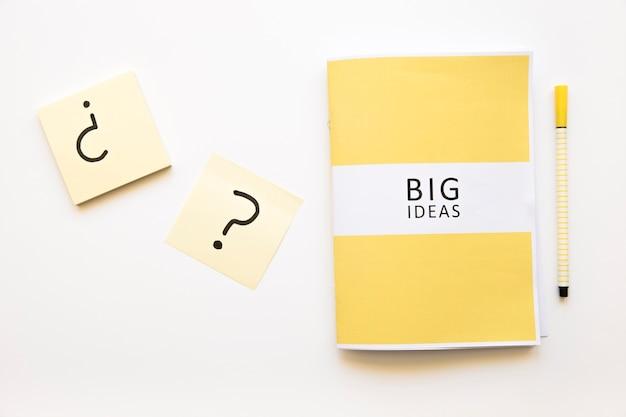 Pense-bête avec signe de point d'interrogation près de grandes idées journal et stylo Photo gratuit