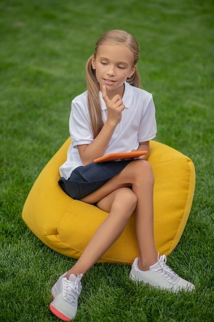 En Pensées. Jolie écolière Blonde Assise Sur Une Chaise De Sac Et à La Réflexion Photo Premium