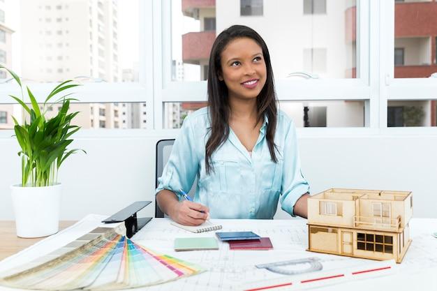 Pensif dame afro-américaine sur une chaise, prenant des notes près du plan et modèle de maison sur la table Photo gratuit