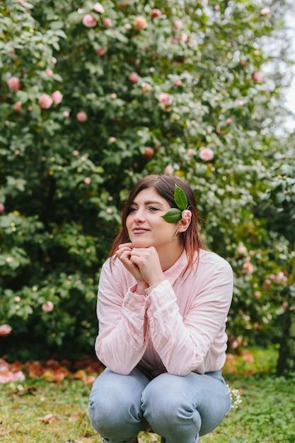 Pensif femme positive avec la plante dans les cheveux près des fleurs roses poussant sur des brindilles vertes Photo gratuit
